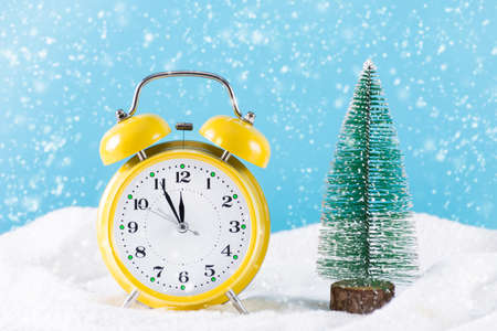 Retro clock and Christmas fir tree on snow and it's snowing winter day. Clock is in yellow color and snowflakes falling. Christmas and New Year holiday time concept