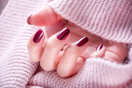 Red wine color manicure on girl hand. Shade of red on woman finger nails polish and woolen scarf background. Close up, selective focus