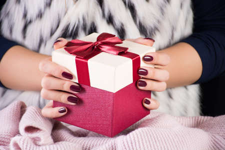 Girl holding red gift present box with tie bow in hands. Woman in fur waistcoat with zebra pattern. Christmas and New Year holiday concept. Close up, selective focus