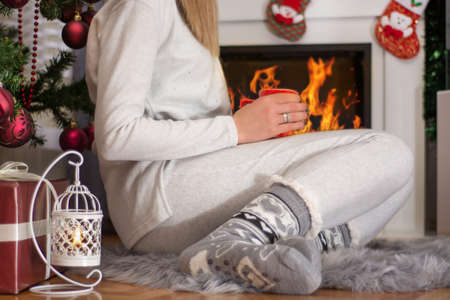 Young girl in Christmas socks and pajamas sitting near fireplace and decorated Xmas tree on furry carpet. Girl holds cup of tea and heat on fire. Christmas and New Year concept