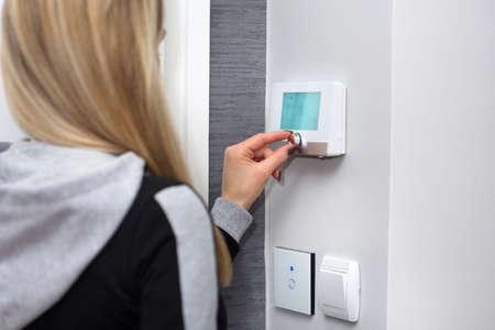 Dziewczyna reguluje i reguluje temperaturę w pomieszczeniu za pomocą inteligentnego przełącznika na ścianie. Inteligentny włącznik światła WiFi i regulator temperatury. Koncepcja inteligentnego domu. Zbliżenie, selektywne skupienie Zdjęcie Seryjne