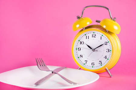 Old alarm clock and empty plate with fork and knife isolated on pink background. Food and Chrono nutrition diet concept. Close up, selective focus Фото со стока