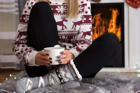 Girl sitting in front of the fireplace and drinking hot tea at home in long winter night. Woman wears woolen winter sweater and socks. Winter and cold weather concept. Close up, selective focus