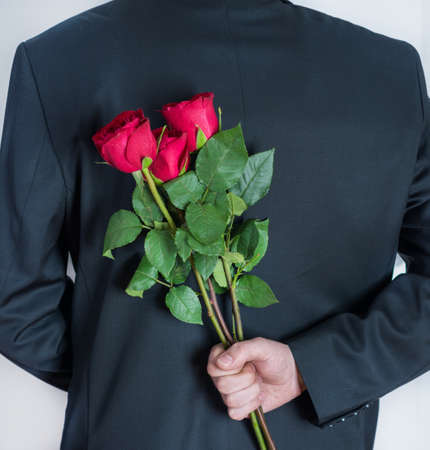 Elegant man holding red rose flowers in hand behind his back. Surprised gift for woman. Romantic and valentines day holiday concept. Close up, selective focus