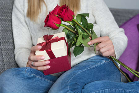 Girl sitting in bed and holding red rose and gift box in hands on legs at home. Woman day and Valentines day concept. Close up, selective focus 写真素材 - 117499797