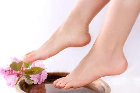 Piernas y pies de niña con pedicura francesa en estudio de belleza y spa en recipiente de madera con agua y decoración de flor rosa. Concepto de spa y belleza femenina. De cerca, enfoque selectivo