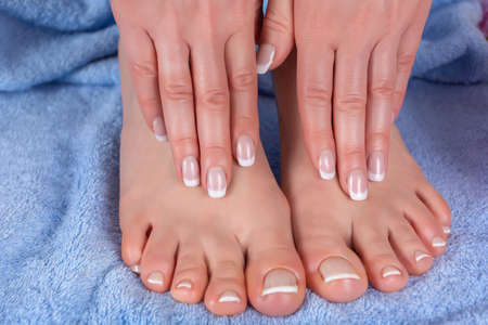 Pedicure and manicure girl feet and hands on blue towel in beauty and spa studio. Woman french nails polish concept. Close up, selective focus