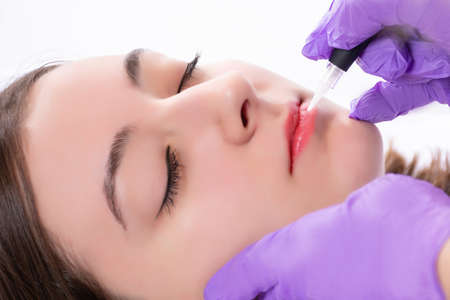 Beautiful young girl getting tattoo red lips in beauty studio. Professional cosmetologist making permanent make up with tool in purple gloves. Close up, selective focus