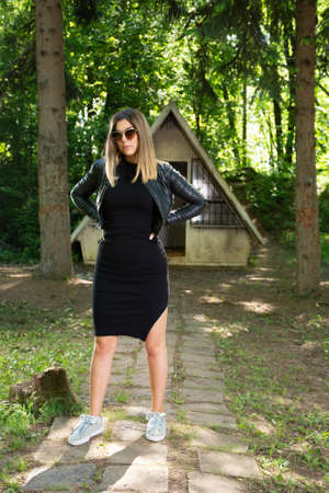 Beautiful fashion model girl with sunglasses, black dress and leather jacket in nature with hands on hips. Small mountain house and forest in the background. Fashion and beauty concept