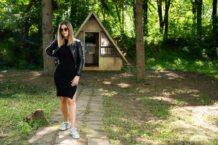Beautiful fashion model girl with sunglasses, black dress and leather jacket in nature. Small mountain house and forest in the background. Fashion and beauty concept