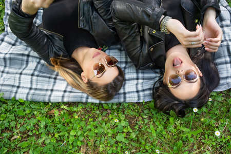 Two happy girls lying down on blanket in a green meadow on a spring day in nature. Girls wear sunglasses and a black jacket. One girl loll out tongue. Close up, selective focus