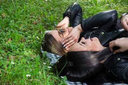 Two happy girls lying down on the blanket and talking in a green meadow on a spring day in nature. Girl wear sunglasses and a black jacket. Relaxation and enjoy concept