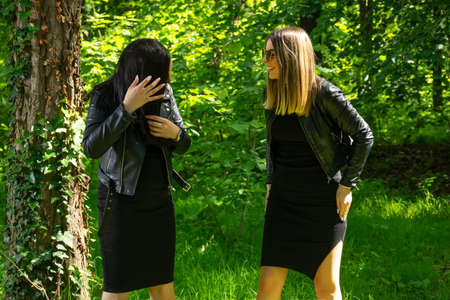 Two happy girls laugh with teeth smile on spring sunny day in the forest. One girl change hair. Girls wear a black dress and leather jacket. Close up, selective focus 写真素材