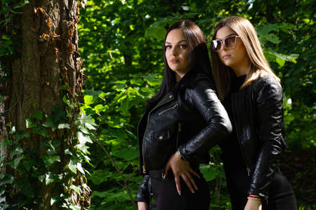 Two beautiful girls posing in a forest on a sunny spring day. The girl wears a black dress and a leather jacket. Forest in background. Close up, selective focus