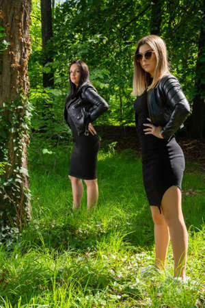 Two beautiful girls posing in a forest on a sunny spring day. The girl wears a black dress and a leather jacket. One girl is in focus. Forest in background 写真素材
