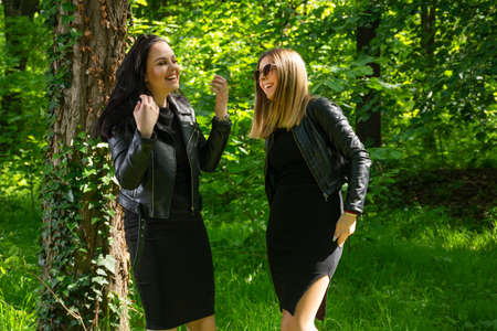 Two happy girls laugh with teeth smile on spring sunny day in the forest. Girls wear a black dress and leather jacket. Close up, selective focus