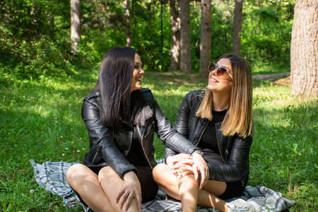 Cute happy girls talking in nature and sitting in the meadow on a blanket, woman laugh and enjoy on a beautiful spring day, park forest in the background. Close up 写真素材