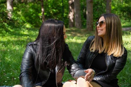 Happy girls talking in nature and sitting in the meadow, girls smiling and enjoy on a beautiful spring day, forest in the background. A woman wears a black dress and jacket 写真素材