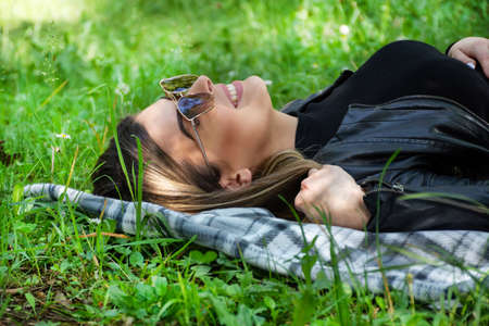Happy woman with sunglasses lying on a blanket in meadow grass on spring sunny day. Girl smiling with teeth and looking up. Relaxing and enjoying in nature concept. Close up, selective focus