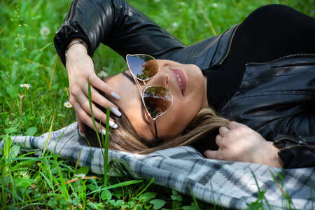 Happy girl with sunglasses lying on a blanket in meadow grass on spring sunny day. Girl smiling with teeth and looking at camera. Relaxing and enjoying in nature concept. Close up 写真素材