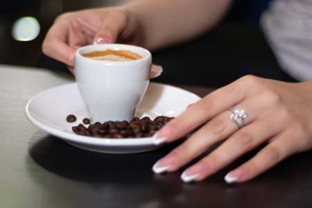 Girl hand holding espresso coffee cup on the desk in a bar. On saucer is blurred roasted coffee beans. Enjoying coffee concept. Close up, selective focus