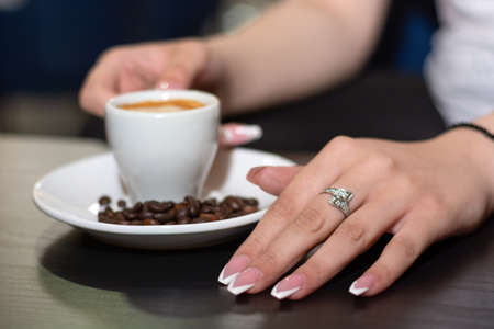 Girl hand with french nails polish manicure with espresso coffee cup on the desk in a bar on the saucer and blurred roasted coffee beans and cup. Close up, selective focus