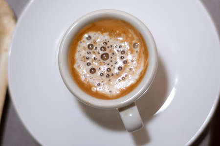 Top view of espresso coffee in a white cup on a saucer. Brown coffee with milk and bubble. Close up, selective focus