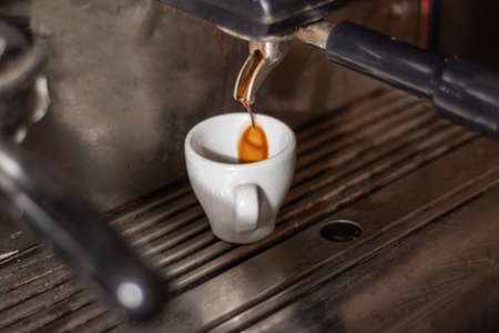Coffee cup on an espresso machine and coffee drip in a cup. Process of making espresso coffee on the old machine in a pub kitchen. Close up, selective focus
