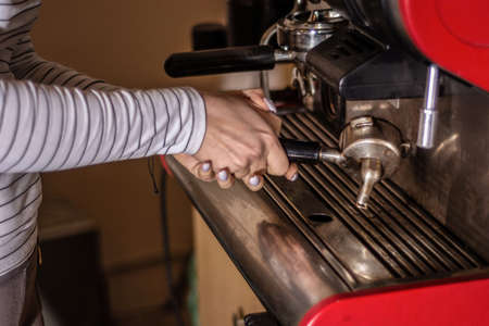 Woman making espresso coffee on a professional machine in the bar. The process of making espresso coffee on the retro machine. Close up, selective focus