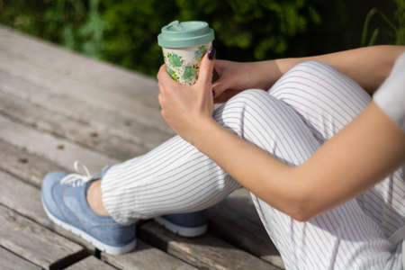 Girl hands holding a cup of coffee on legs in striped pants and sitting on a bench in the park on spring sunny day. Relaxation and enjoy businesswoman concept. Close up, selective focus