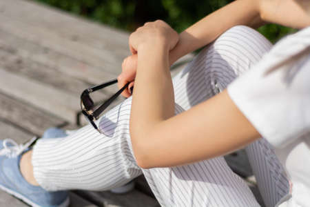 Girl hands holding sunglasses on legs with striped pants and sitting on a bench in the park on spring sunny day. Relaxation and enjoy businesswoman concept. Close up, selective focus