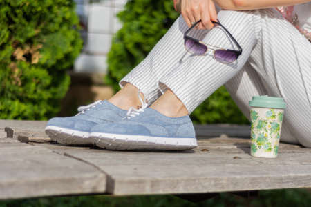 Fashionable woman with striped pants and blue sneakers sitting on a bench in the park and holding sunglasses, coffee cup next to girl legs. Femininity fashion concept. Close up, selective focus