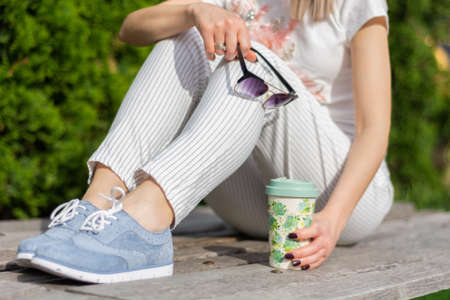 A modern girl with striped pants and blue sneakers and little bare skin on legs holding sunglasses and a cup of coffee. A woman sitting on a bench in a park on a spring day. Close up, selective 写真素材