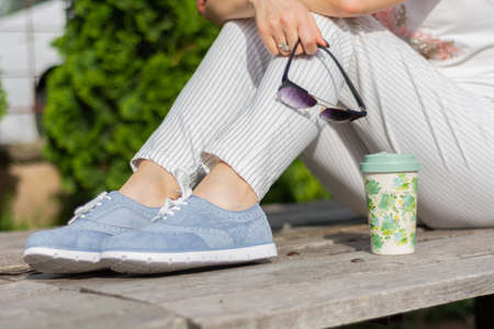 A modern woman with striped pants and blue sneakers sitting on a bench in the park and holding sunglasses, coffee cup next to girl legs. Femininity fashion concept. Close up, selective  focus 写真素材