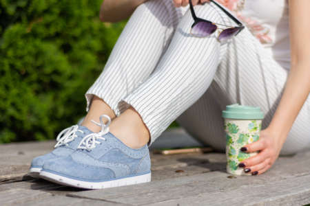 Fashionable girl legs with striped pants and blue sneakers and little bare skin on legs holding sunglasses and cup of coffee. Woman sitting on bench in park on spring day. Close up, selective