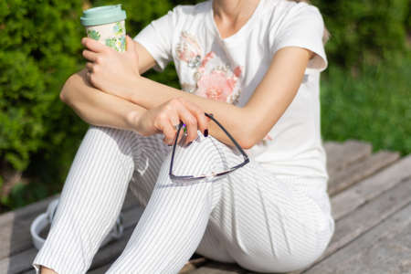 Young woman holding a cup of coffee and sunglasses on legs with modern fashionable striped pants. Girl sitting on a bench in the park. Relaxing on a spring day. Close up, selective focus