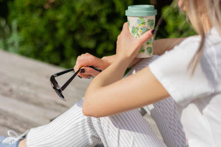 Girl holding a cup of coffee and sunglasses in hands on legs and sitting on bench in park. A woman wears modern striped pants and t short. Relaxing on a spring day. Close up, selective focus 写真素材