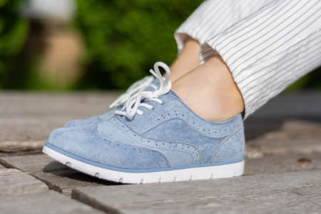 Female legs with blue sneakers on a wooden bench in the park on a spring day. A girl wears striped pants and little bare skin around the legs wrists. Close up, selective focus