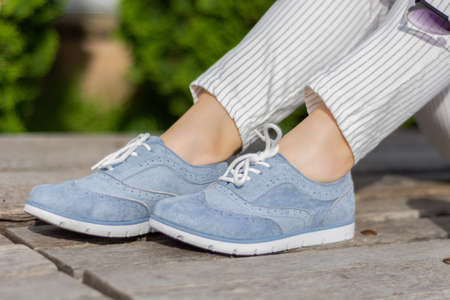 Modern woman legs with blue sneakers on a wooden bench in the park on a spring day. A girl wears striped pants and little bare skin around the legs wrists. Close up, selective focus 写真素材