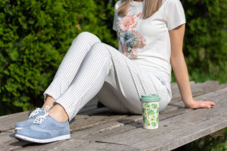 Modern woman in striped pants, blue sneakers and t shirt sitting on bench next to a cup of coffee relaxing in the park. Spring summer clothes vogue style concept. Close up, selective focus