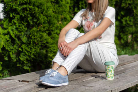 High fashion female in striped pants, blue sneakers and t shirt sitting on the bench next to the cup of coffee and resting. Spring summer clothes vogue style concept. Close up, selective focus