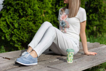 High fashion girl in striped pants, blue sneakers and t shirt sitting on bench next to a cup of coffee resting in the park. Spring summer clothes vogue style concept. Close up, selective focus