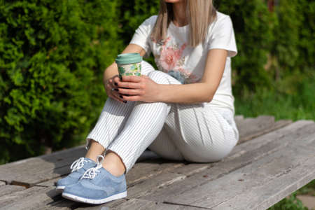 High fashion woman in striped pants, blue sneakers and t shirt sitting on the bench and holding cup of coffee and resting. Spring summer clothes vogue style concept. Close up, selective focus 写真素材