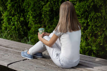 Young woman sitting on bench with striped pants and holding cup of coffee. Girl resting in the park on good weather. Spring summer clothes vogue style concept. Close up, selective focus