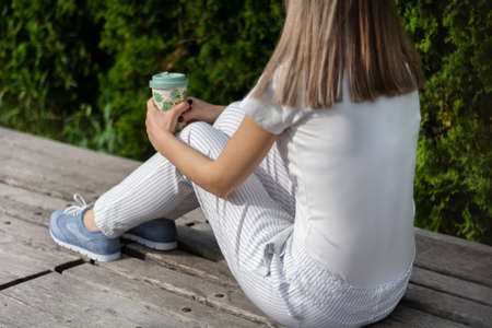 Fashionable girl sitting on bench with striped pants and holding cup of coffee. Woman resting in the park on good weather. Spring summer clothes vogue style concept. Close up, selective focus