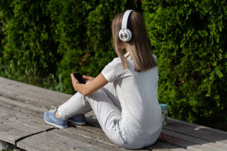 Young woman listening to music on a headphone and using a smartphone. A woman sitting on the bench in the park on a sunny spring day. Fashionable female in striped pants. Close up, selective focus