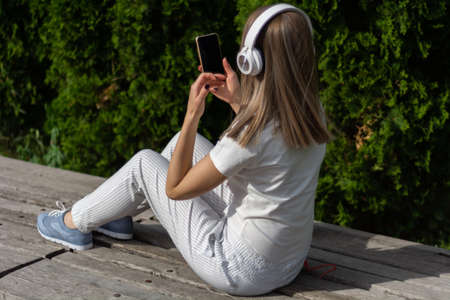 Young girl listening to music on a headphone and looking in a smartphone. A woman sitting on the bench in the park on a sunny spring day. Female in striped pants. Close up, selective focus