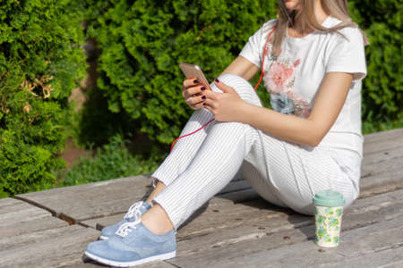 Girl using a smartphone. A woman sitting on the bench next to a cup of coffee in the park on a sunny spring day. Fashionable female in striped pants and blue sneakers. Close up, selective focus