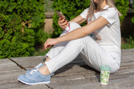 Young girl looking in smartphone and sitting on the bench next to a cup of coffee in the park on a sunny spring day. Fashionable female in striped pants and blue sneakers. Close up, selective focus