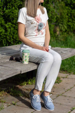 Girl in striped pants and blue shoes sitting on a wooden bench next to a cup of coffee and sunglasses in the park on spring sunny day. Fashionable vogue style concept. Close up, selective focus